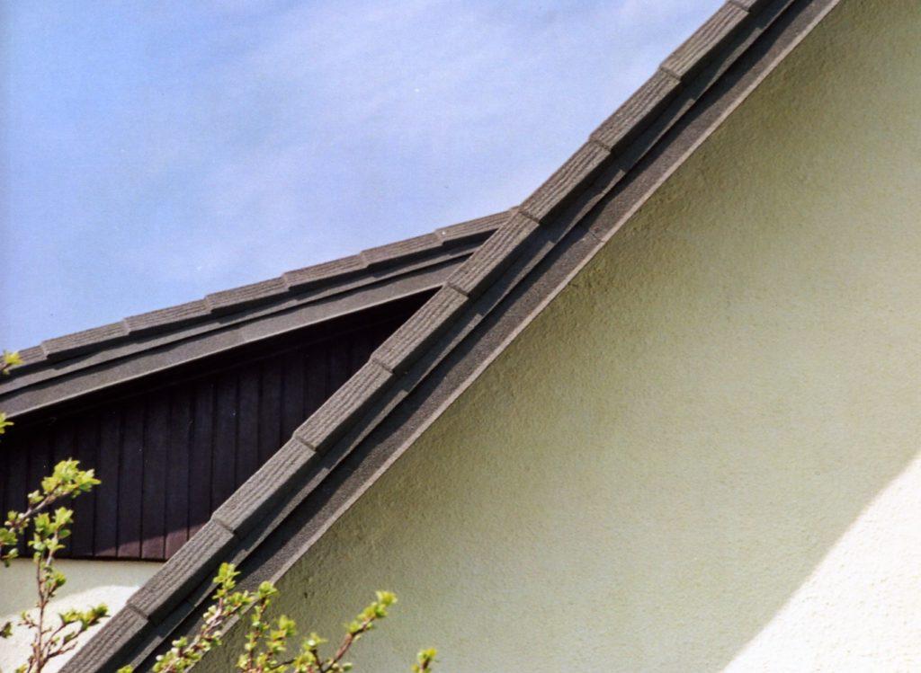 Ostre różnice wkątach nachylenia połaci jednegp dachu.  Dachówka ceramiczno-metalowa Gerard AHI.